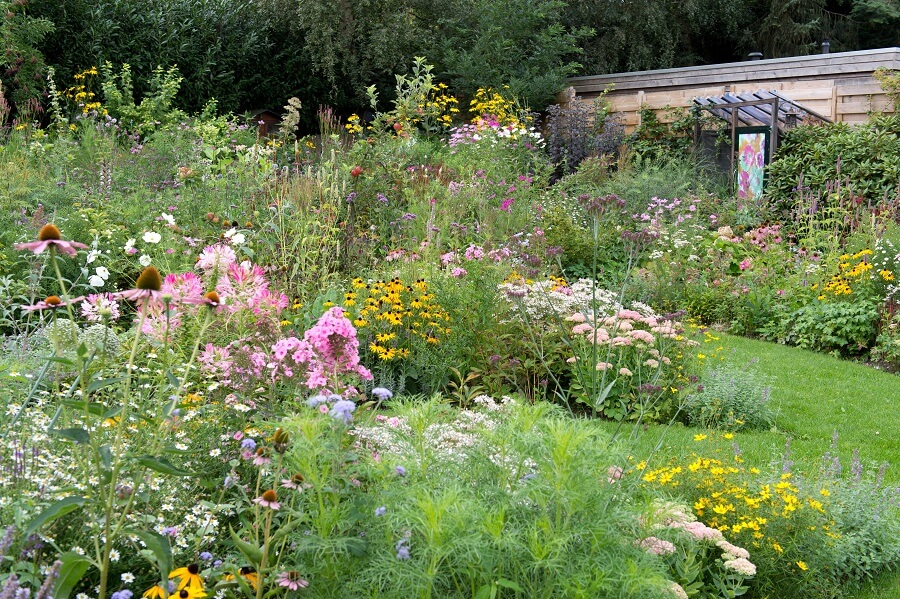 Ingrid heeft een symmetrische tuin door de mandalavorm, maar de bloemen en planten maken het heel vrolijk en speels – Tuinieren met Buitenleven